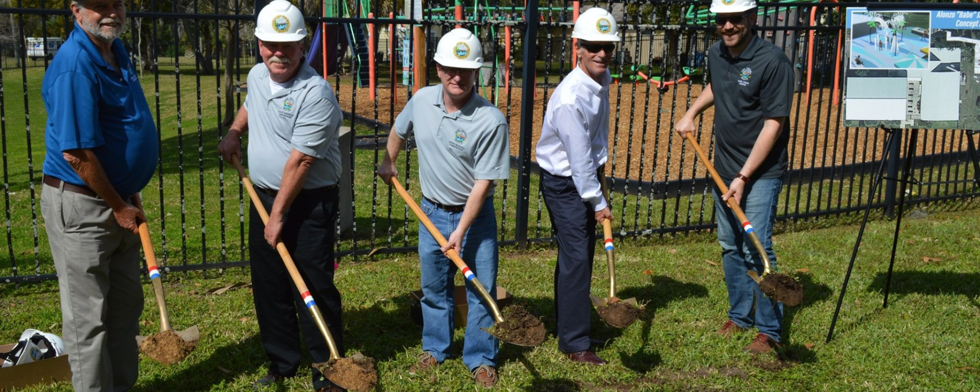 men and women with hard hats and shovels for community groundbreaking ceremony