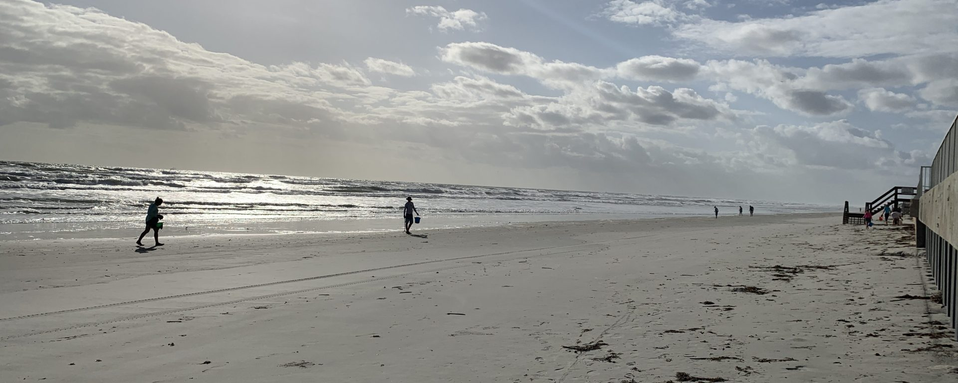 empty beach in Volusia County with a couple of people walking