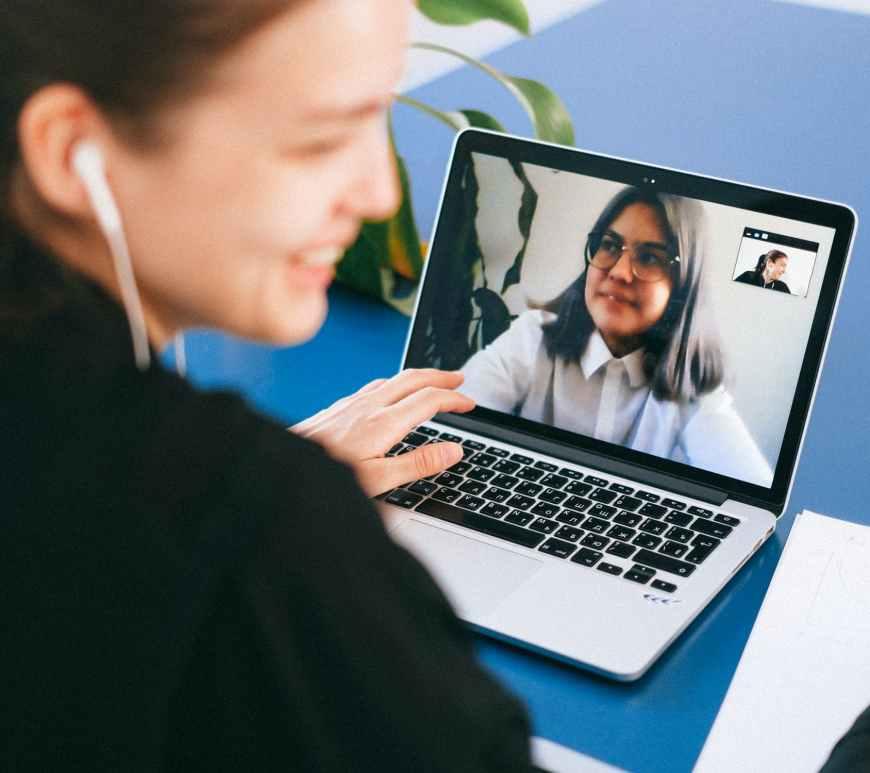 woman sits at computer on video chat with another woman