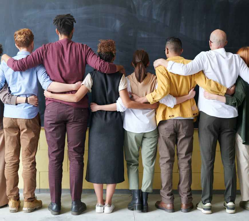 group of mixed race and mixed gender people standing together with backs turned
