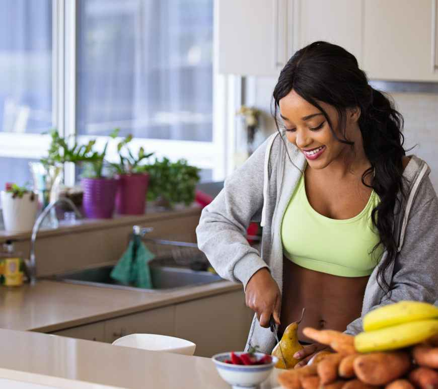 smiling woman stands at kitchen counter chopping fruits and vegetables after working out