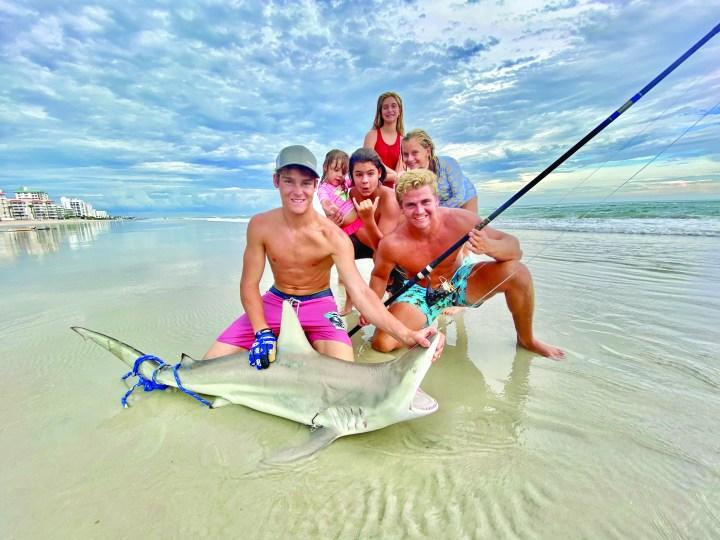 group of kids on beach surrounding black tip shark