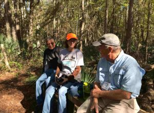 Three community members sitting on a bench in the preserve surrounded by trees.