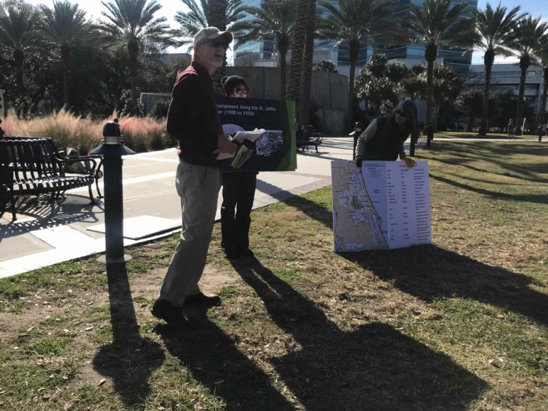 Man speaking with two women holding maps of Jacksonville.