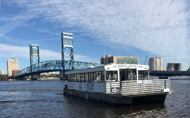 A boat pulling up to a dock on a sunny day with a blue bridge in the background.