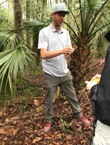A man holding fiber strands from palmetto leaves.