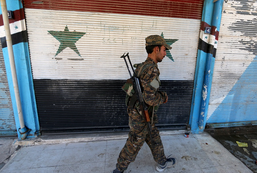 A Kurdish fighter from the People's Protection Units (YPG) walks past a shop with Syrian national flags painted on its shutter in the southeast of Qamishli city, Syria, April 22, 2016. REUTERS/Rodi Said