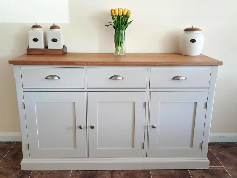 Edmunds Painted 5ft Sideboard handmade from Edmunds & Clarke Furniture. Painted in Dunwich stone with a solid square oak top, 3 drawers and 3 doors, image showing cup chrome cup handles and chrome knobs EDM029