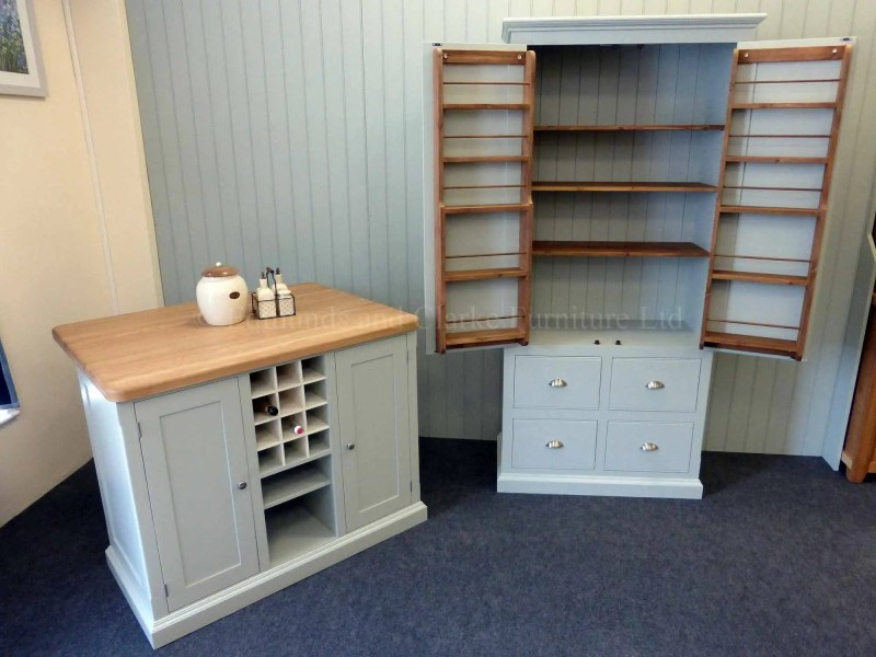 Edmunds painted 4ft x 3ft kitchen Island in Southwold Sky Blue. Solid oak top. Central shelves and wine rack with 2 paneled doors and on other side a overhang for stools. Image showing edmunds larder cupboard to match EDM008