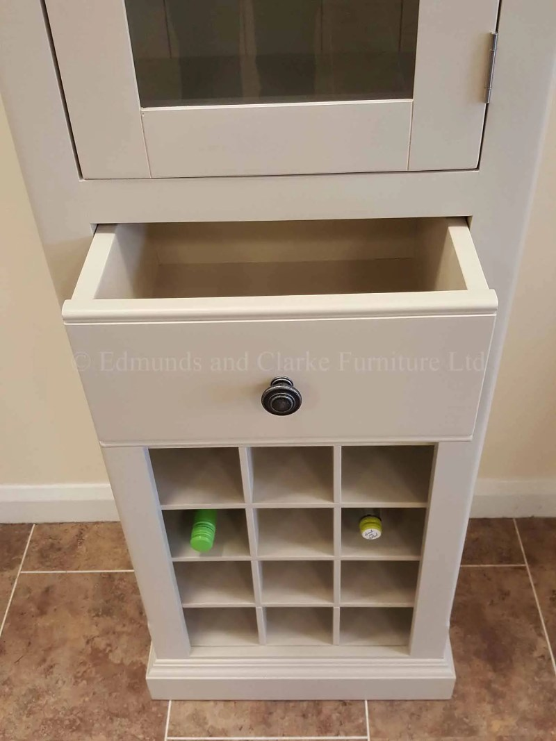 Narrow glazed kitchen cupboard with wine rack below and drawer above