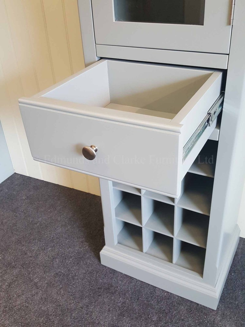 Tall glazed narrow cupboard with wine rack for twelve bottles drawer above and large glazed door with