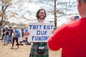 "man holding a sign that reads ""They Kilt our funding"". He is also wearing a kilt"