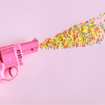 a pink gun shooting rainbow sprinkles out of it