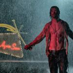 "A shirtless man with abs standing in front of a neon sign that says ""See You Again Soon"""
