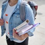 Girl carrying books and a backpack