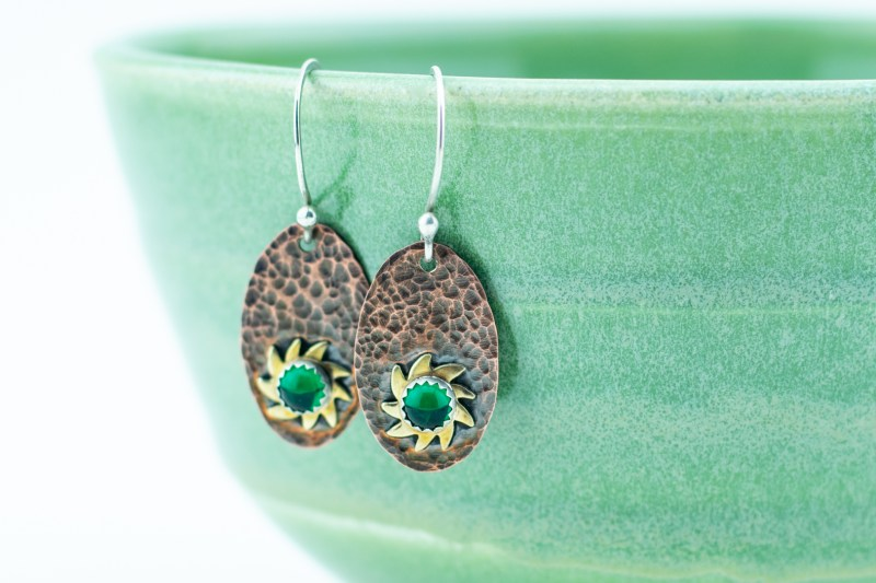 hammered copper sunburst earrings with green glass cabochons and patina
