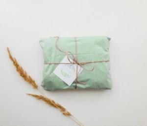 cadeau emballé dans du papier recyclé attaché avec une ficelle marron et fine et des brins de blé