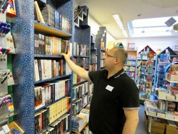 Marco Runge sortiert Bücher im Regal.