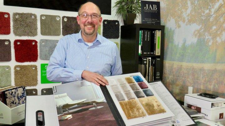 Alexander Ambros zeigt ein Buch mit Materialproben für Teppichboden.