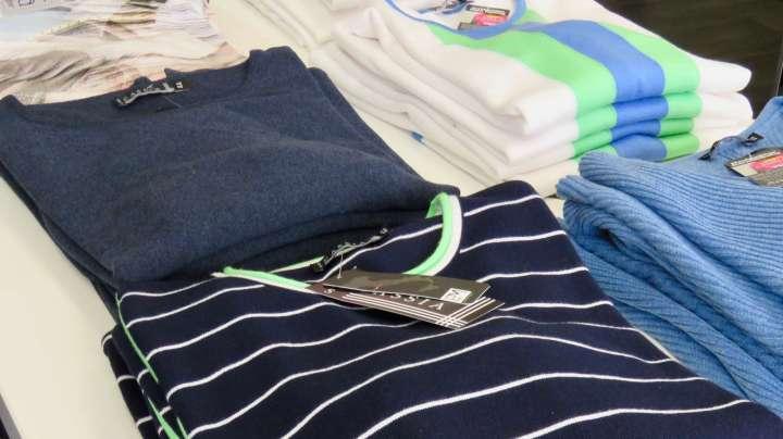 """Auf dem Tisch liegen modische Shirts in der Frühlingsfarbe """"Blau""""."""