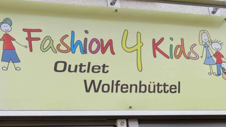 """Über dem Eingang hängt das Schild """"Fashion 4 Kids Outlet Wolfenbüttel""""."""