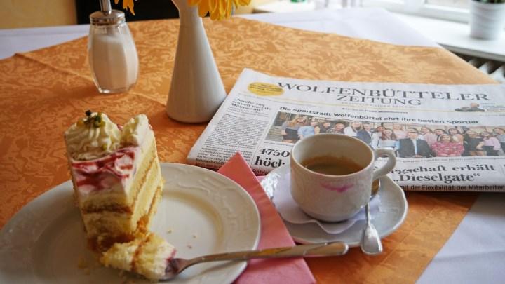 Ein Stück Torte, Tasse Kaffee und Zeitung liegen auf dem Tisch