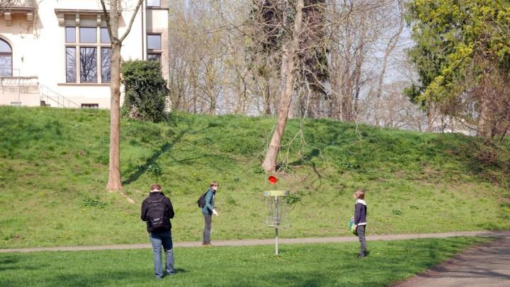Zwei Kinder spielen mit ihrem Vater Discgolf im Seeligerpark. In der Mitte ist ein Discgolf-Korb zu sehen, eine Scheibe fliegt durch die Luft. Im Hintergrund ist ein Teil der Seeligervilla zu sehen.