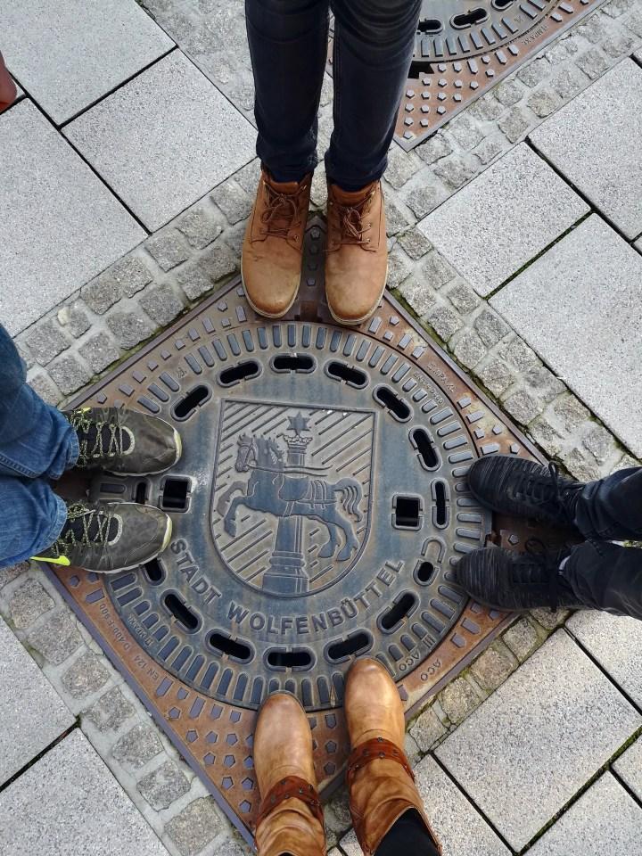 Ein Gulli-Deckel von oben mit dem Wolfenbütteler Stadtwappen. An vier Seiten sind Füße zu sehen.