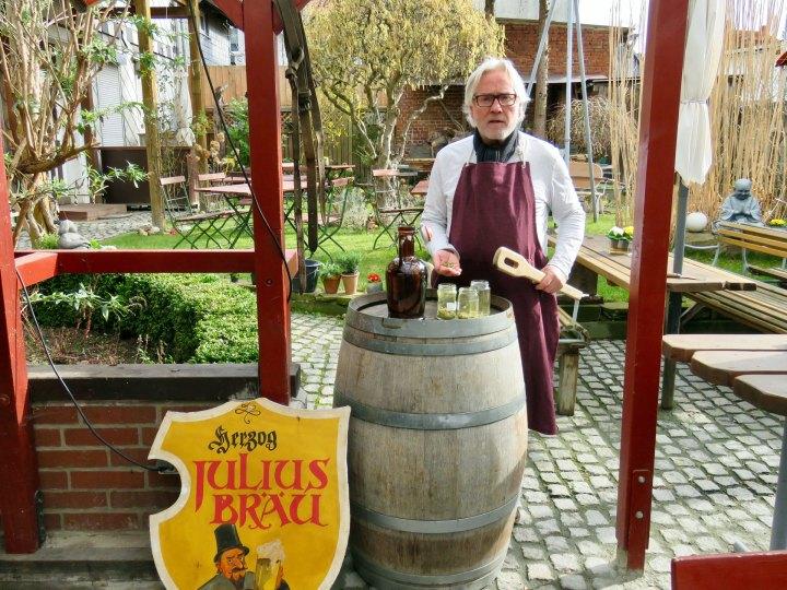 Michael Stier steht mit Brauschürze hinter eine alten Bierfass.