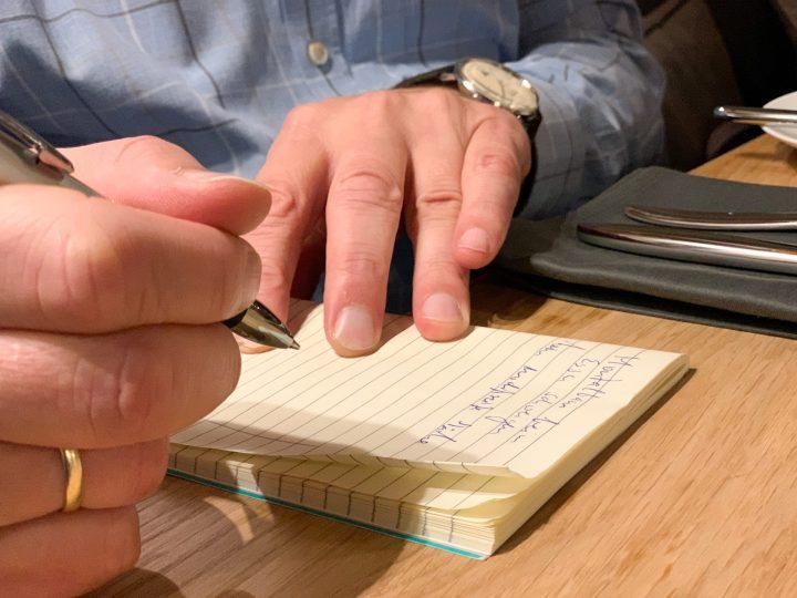 In einem Notizbuch wird alles notiert.