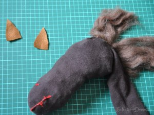 After I hand stitched a nose and mouth onto the horse, I cut out two triangles of felt for the ears..