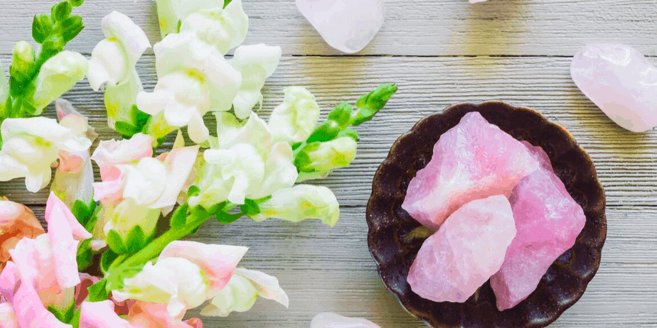 Beautiful spring flowers and rose quartz on a light wood table