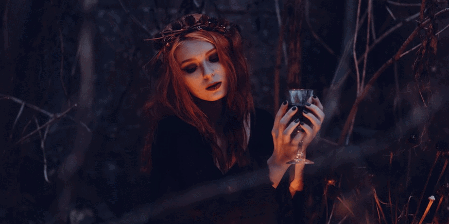 A witchy woman holding a goblet and wearing a tiara in the forest at night