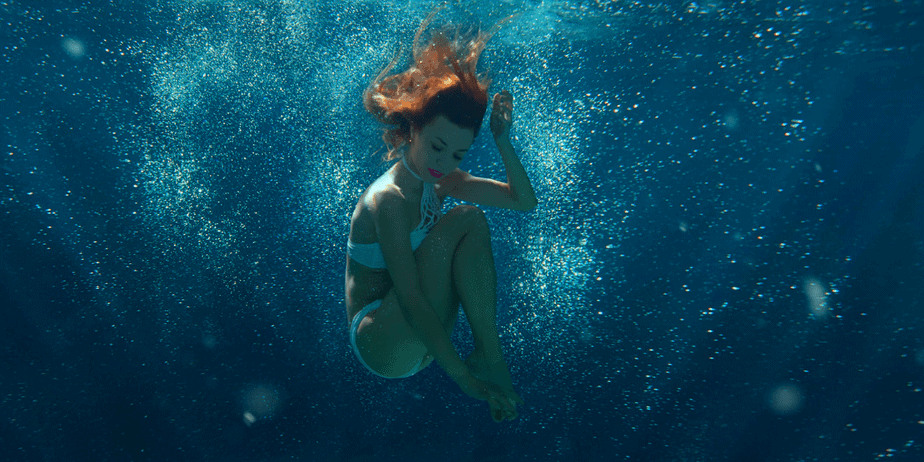 A woman with red hair diving into a deep, dark pool of water