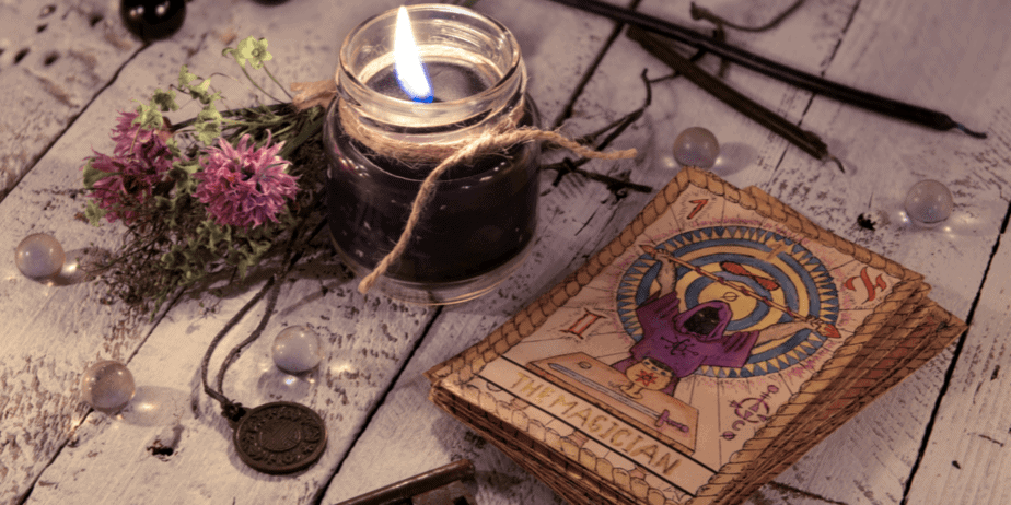 Tarot cards, a candle, and other occult items on a wooden table