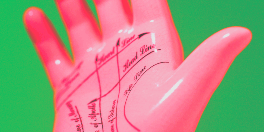 A pink fake hand with chiromancy lines against a green background