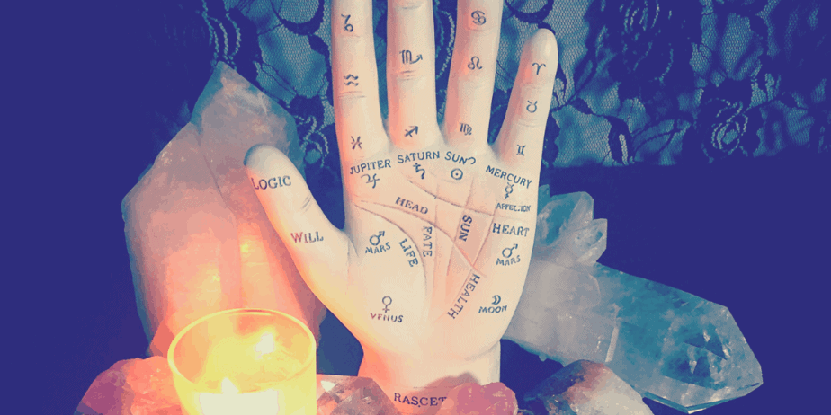 A ceramic hand with palm reading symbols painted on it surrounded by crystals and a candle
