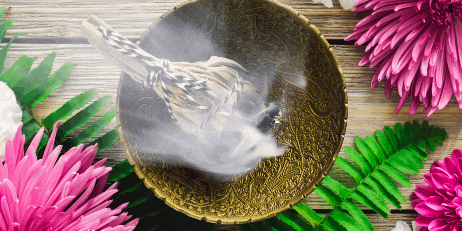 Sage placed in a bowl, burning with smoke and surrounded by flowers and plant fronds