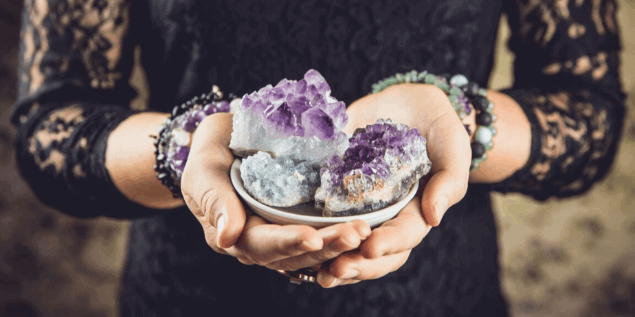 A woman holding a bowl of assorted crystals