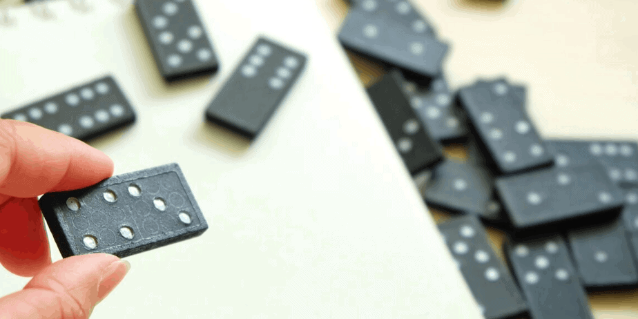 A hand holding black and white dominoes