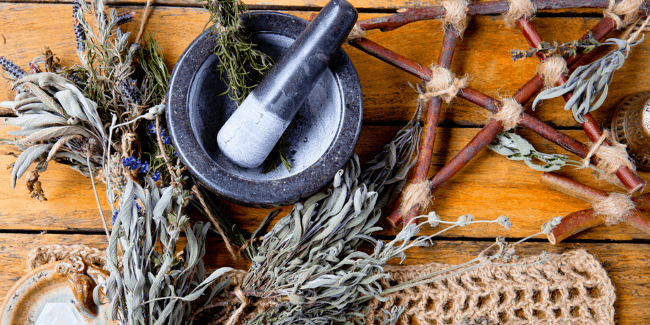 Herbs and a mortar and pestle on a table with a DIY pentacle
