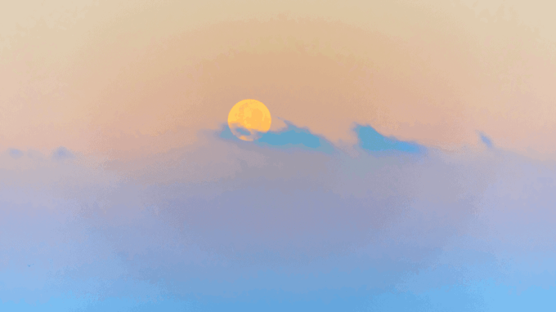 Decorative image of the moon behind colorful clouds