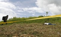 A police officer walks near the body of a journalist at the scene of a massacre of a political clan, which included several journalists, on the outskirts of Ampatuan, Maguindanao in southern Philippines, November 24, 2009. Philippine President Gloria Macapagal Arroyo placed two southern provinces and a city under emergency rule on Tuesday after 24 people were killed in the worst-ever election related violence in the country. REUTERS/Erik de Castro (PHILIPPINES CRIME LAW CONFLICT)