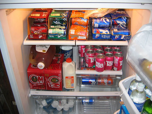 A refrigerator packed with cans of soda.