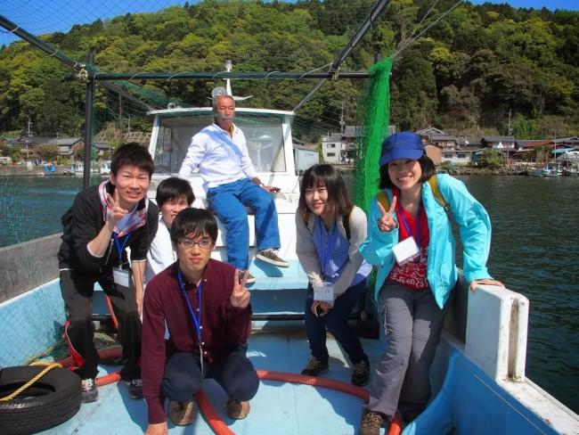 船に乗って対岸の港へ行く学生ボランティア