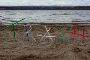 Trash written with straws on the beach