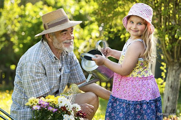Happy grandfather with his granddaughter working in the garden