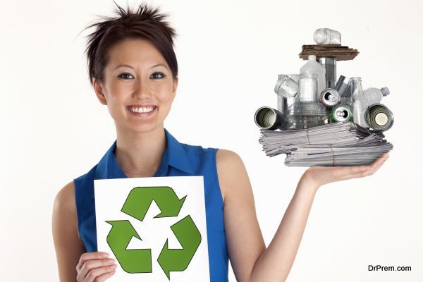 Pretty Asian Woman holding up a Recycle sign and recyclables