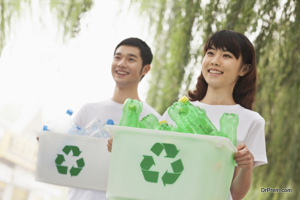 Two Young People Recycling Plastic Bottles