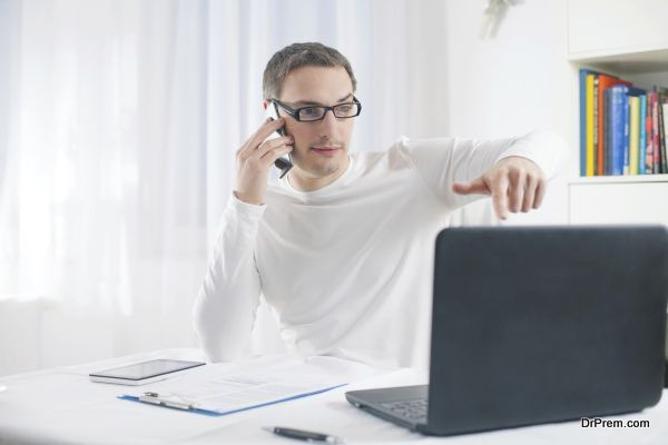 Young businessman working at home using laptop and mobile phone